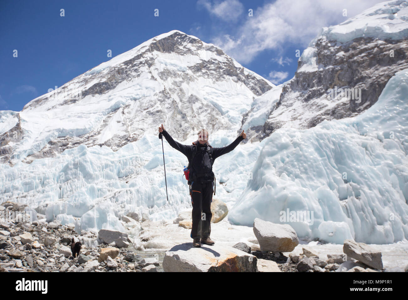 Happy male hiker with his hands in air in Everest Base Camp, Khumbu, Nepal - Stock Image