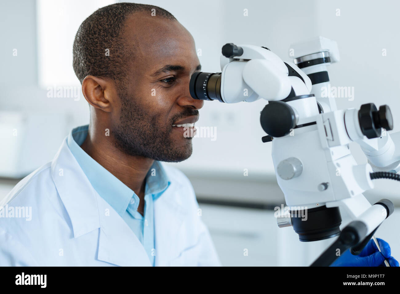 Upbeat man studying oral cavity with help of microscope - Stock Image