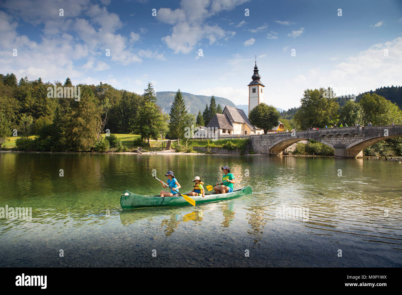 Family in canoe on Lake Bohinj, with church and bridge of Ribcev Laz in background, Triglav, Slovenia - Stock Image