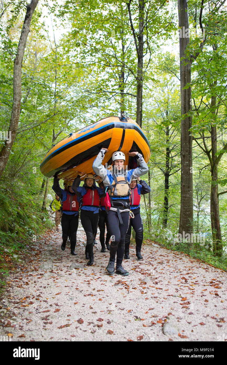 Group of rafters carrying inflatable boat over their heads to river Soca near Bovec, Triglav, Slovenia - Stock Image