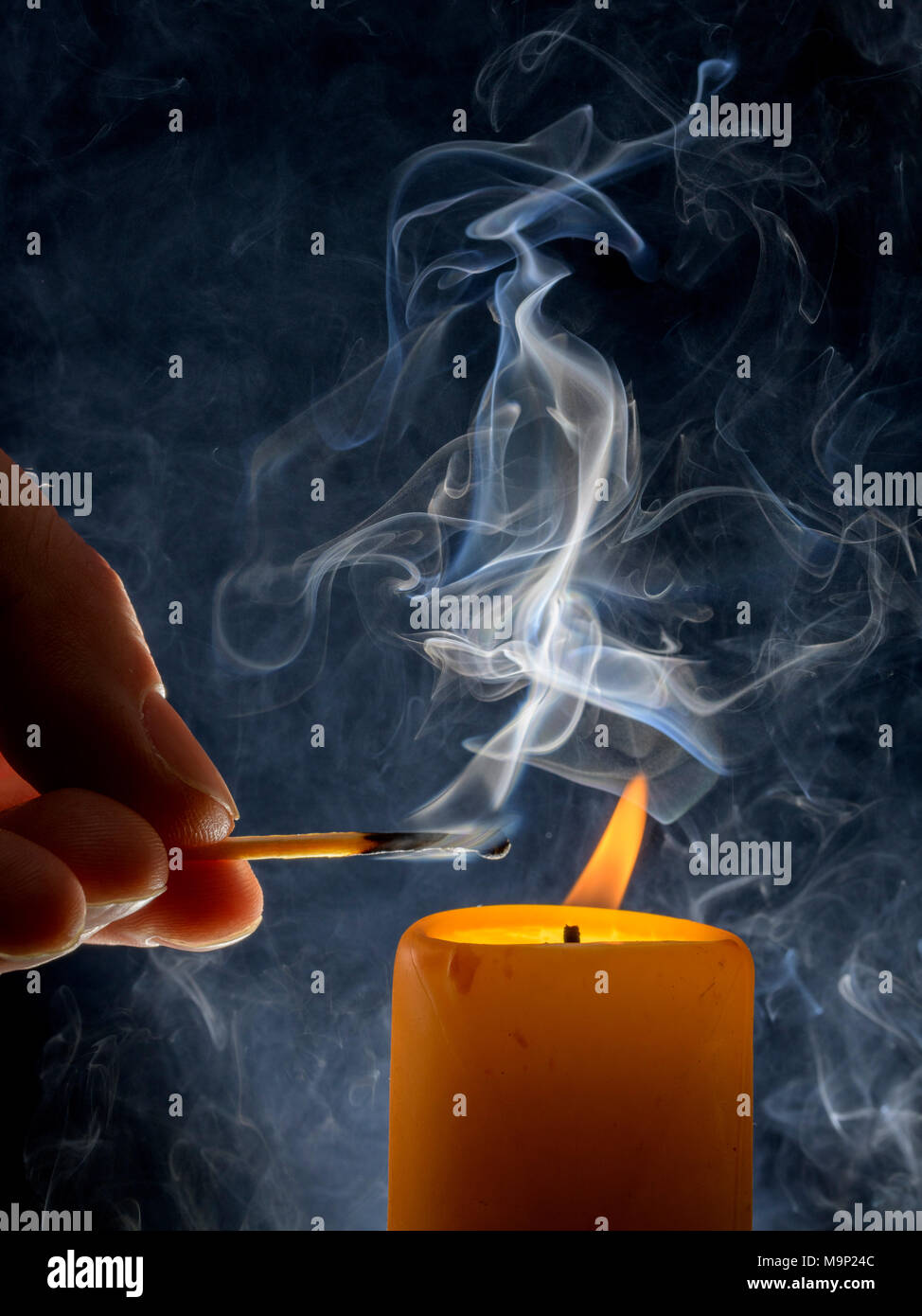 Lighting of a candle with smoking match in front of a black background, studio shot - Stock Image