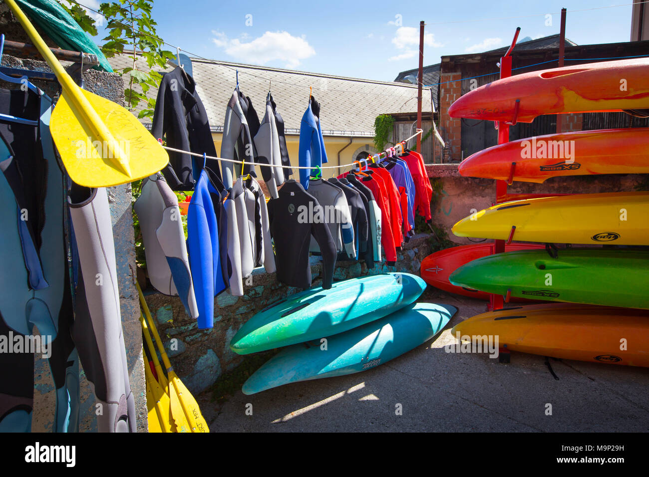 Kayaks, canoes, wetsuits and peddles are drying in the backgarden of water sports company Sport Mix in Bovec. The emerald Soca in Slovenia, originating in the Triglav mountains, is famous for all kinds of white water activities. - Stock Image