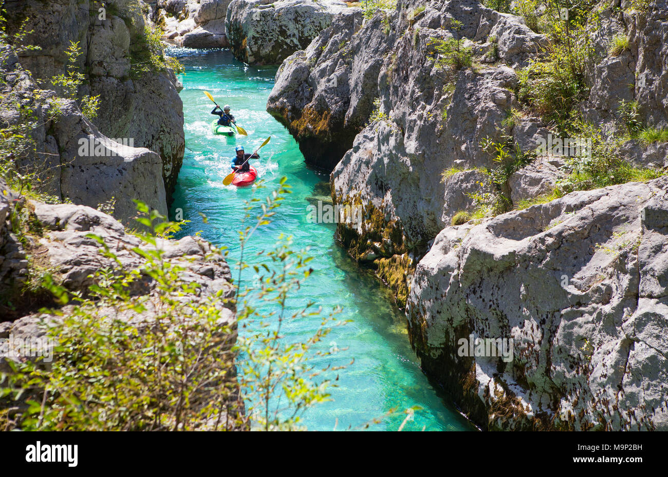 Kayakkers on the emerald Soca near Bovec in Slovenia. This green colored river, originating in the Triglav mountains, is famous for all kinds of white water activities. - Stock Image