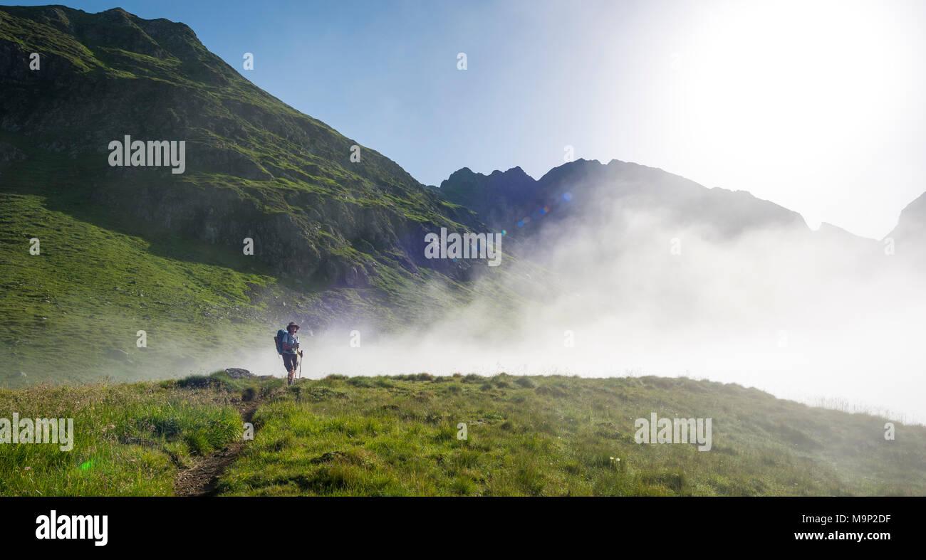 Hiker on the Schladminger Höhenweg with rising clouds of fog, Schladminger Tauern, Schladming, Steiermark, Austria - Stock Image