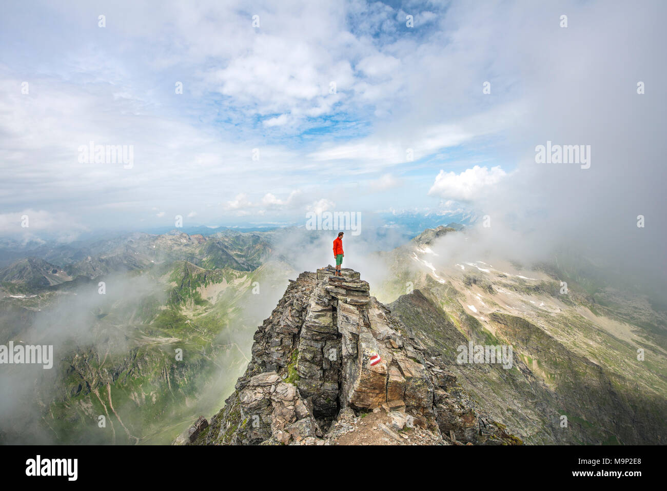 Hiker on the summit of the Hochgolling with rising fog, Schladminger Höhenweg, Schladminger Tauern, Schladming, Steiermark - Stock Image