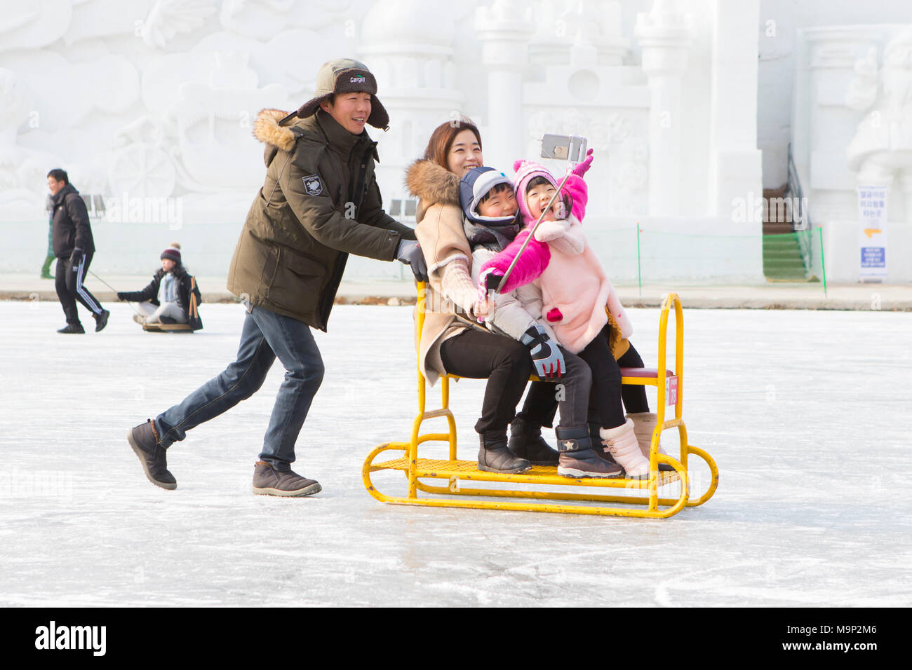 An Asian looking family is having fun taking a selfie on a group sled at the frozen river at the Hwacheon Sancheoneo Ice Festival.  The Hwacheon Sancheoneo Ice Festival is a tradition for Korean people. Every year in January crowds gather at the frozen river to celebrate the cold and snow of winter. Main attraction is ice fishing. Young and old wait patiently over a small hole in the ice for a trout to bite. In tents they can get the fish grilled after which they are eaten. Among other activities are sledding and ice skating.  The nearby Pyeongchang region will host the Winter Olympics in - Stock Image