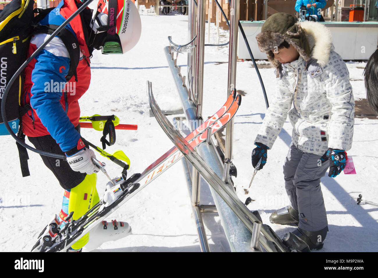 Two children are cleaning their skis with pressurized air pistols in the Alpensia resort, Gangwon-do region, South Korea.  The Alpensia Resort is a ski resort and a tourist attraction. It is located on the territory of the township of Daegwallyeong-myeon, in the county of Pyeongchang, hosting the Winter Olympics in February 2018.  The ski resort is approximately 2.5 hours from Seoul or Incheon Airport by car, predominantly all motorway.   Alpensia has six slopes for skiing and snowboarding, with runs up to 1.4 km (0.87 mi) long, for beginners and advanced skiers, and an area reserved for - Stock Image