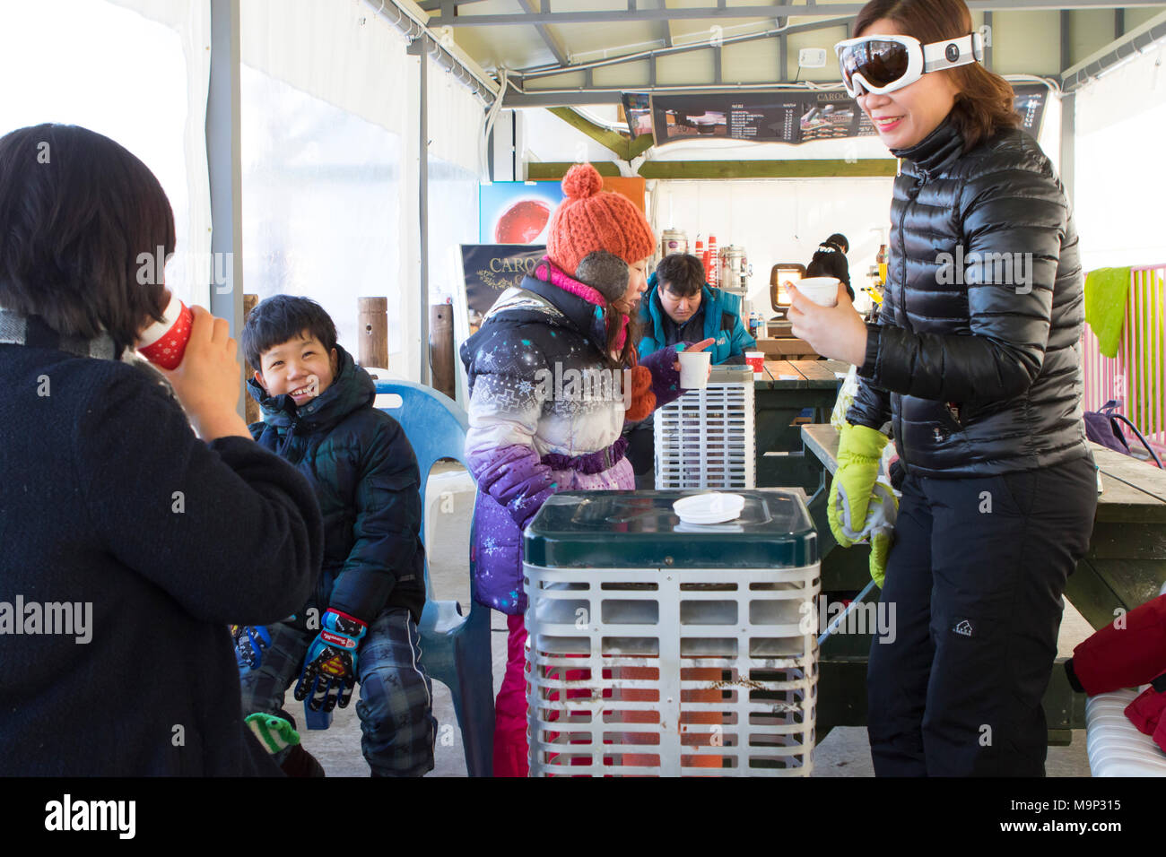 An Asian looking family is warming up inside a tent, next to a heater, with hot chocolate.  Yongpyong (Dragon Valley) Ski Resort is a ski resort in South Korea, located in Daegwallyeong-myeon, Pyeongchang, Gangwon-do. It is the largest ski and snowboard resort in Korea. Yongpyong will host the technical alpine skiing events for the 2018 Winter Olympics and Paralympics in Pyeongchang. Some scenes of the 2002 Korean Broadcasting System drama Winter Sonata were filmed at the resort. - Stock Image