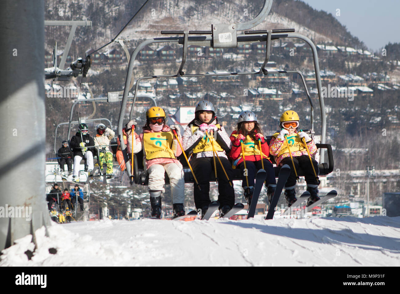 A group of four children is arriving at the chair lift top station of the bunny slope at Yongpyong.  Yongpyong (Dragon Valley) Ski Resort is a ski resort in South Korea, located in Daegwallyeong-myeon, Pyeongchang, Gangwon-do. It is the largest ski and snowboard resort in Korea. Yongpyong will host the technical alpine skiing events for the 2018 Winter Olympics and Paralympics in Pyeongchang. Some scenes of the 2002 Korean Broadcasting System drama Winter Sonata were filmed at the resort. - Stock Image