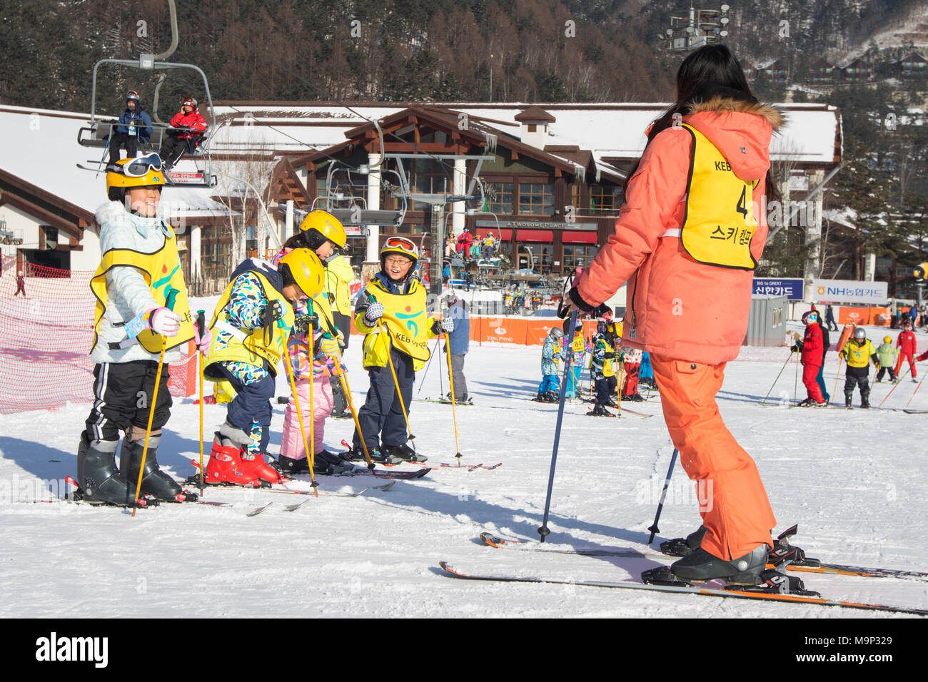 A ski teacher and a group of Asian children at a bunny slope of Yongpyong.  Yongpyong (Dragon Valley) Ski Resort is a ski resort in South Korea, located in Daegwallyeong-myeon, Pyeongchang, Gangwon-do. It is the largest ski and snowboard resort in Korea. Yongpyong will host the technical alpine skiing events for the 2018 Winter Olympics and Paralympics in Pyeongchang. Some scenes of the 2002 Korean Broadcasting System drama Winter Sonata were filmed at the resort. - Stock Image