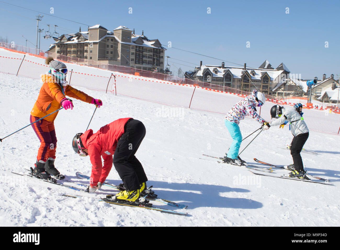 Two women are being taught how to ski on a mellow ski slope of the Alpensia resort in the Gangwon-do region of South Korea.  The Alpensia Resort is a ski resort and a tourist attraction. It is located on the territory of the township of Daegwallyeong-myeon, in the county of Pyeongchang, hosting the Winter Olympics in February 2018.  The ski resort is approximately 2.5 hours from Seoul or Incheon Airport by car, predominantly all motorway.   Alpensia has six slopes for skiing and snowboarding, with runs up to 1.4 km (0.87 mi) long, for beginners and advanced skiers, and an area reserved for - Stock Image