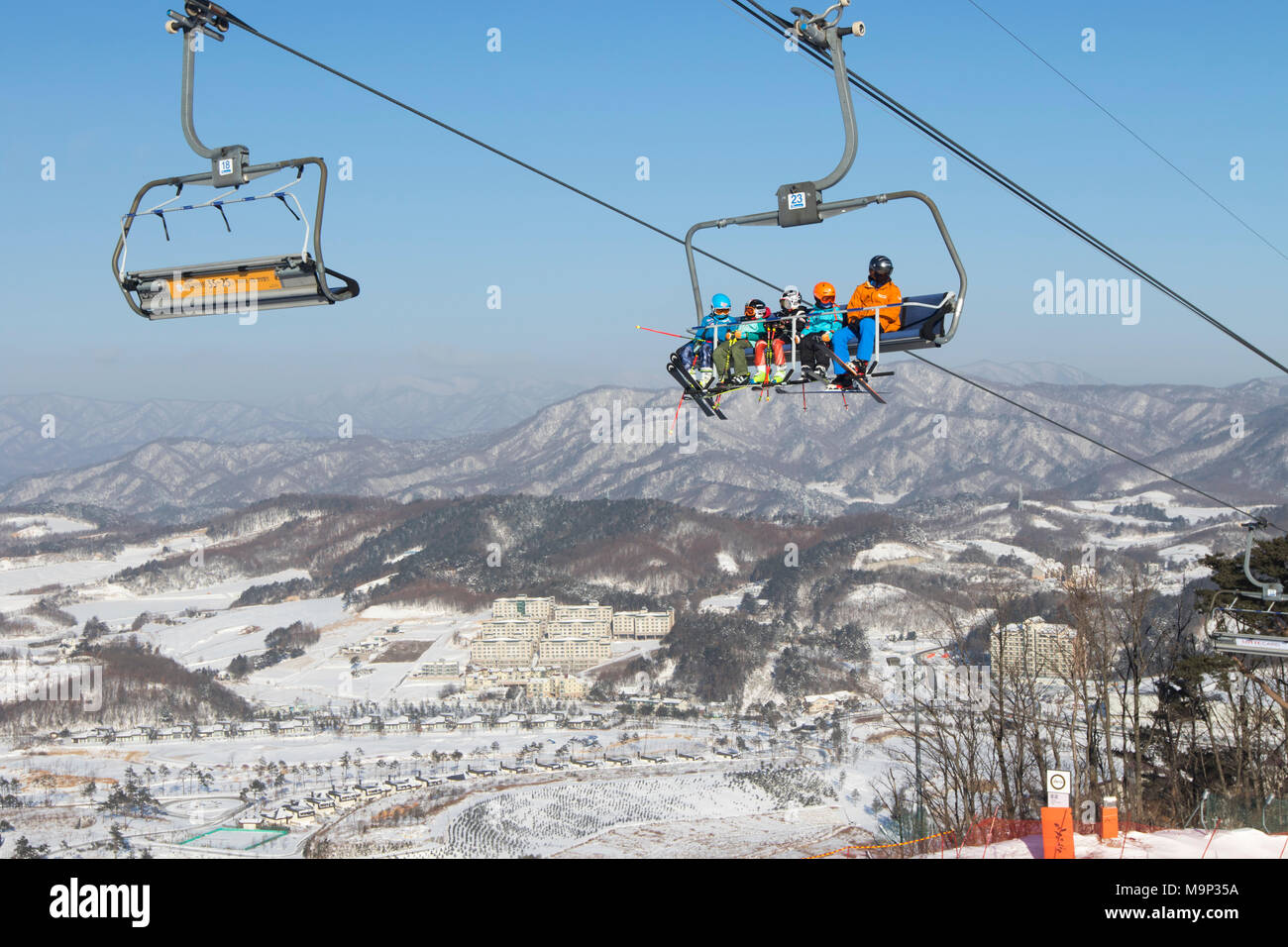 Colorful dressed skiers in a chair lift high above Alpensia resort in the Gangwon-do region of South Korea.  The Alpensia Resort is a ski resort and a tourist attraction. It is located on the territory of the township of Daegwallyeong-myeon, in the county of Pyeongchang, hosting the Winter Olympics in February 2018.  The ski resort is approximately 2.5 hours from Seoul or Incheon Airport by car, predominantly all motorway.   Alpensia has six slopes for skiing and snowboarding, with runs up to 1.4 km (0.87 mi) long, for beginners and advanced skiers, and an area reserved for snowboarders. - Stock Image