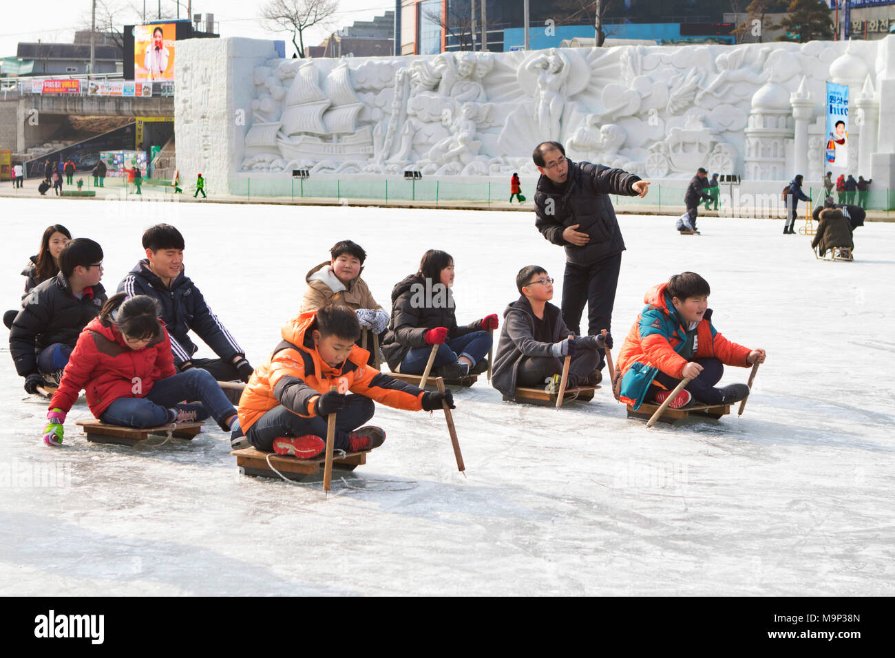 A group of South Korean school children are doing a sledding competition.    The Hwacheon Sancheoneo Ice Festival is a tradition for Korean people. Every year in January crowds gather at the frozen river to celebrate the cold and snow of winter. Main attraction is ice fishing. Young and old wait patiently over a small hole in the ice for a trout to bite. In tents they can let the fish grilled after which they are eaten. Among other activities are sledding and ice skating.    The nearby Pyeongchang region will host the Winter Olympics in February 2018. - Stock Image