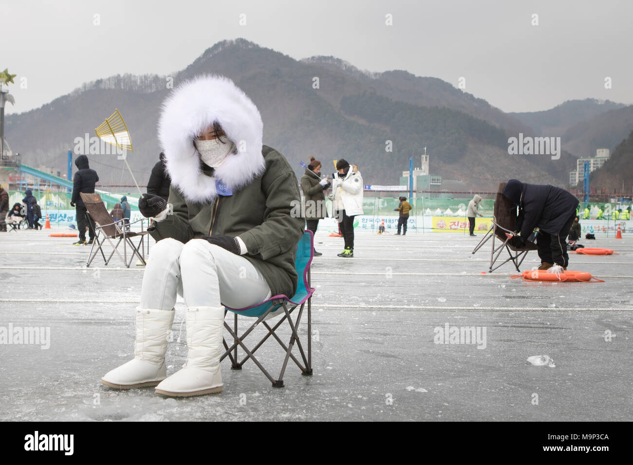 A woman warmly dressed in a thick fur coat is waiting above a hole in the ice during the ice fishing festival at Hwacheon Sancheoneo in the Gangwon-do region of South Korea.  The Hwacheon Sancheoneo Ice Festival is a tradition for Korean people. Every year in January crowds gather at the frozen river to celebrate the cold and snow of winter. Main attraction is ice fishing. Young and old wait patiently over a small hole in the ice for a trout to bite. In tents they can let the fish grilled after which they are eaten. Among other activities are sledding and ice skating.  The nearby Pyeongchang - Stock Image
