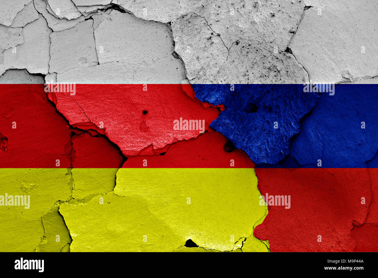 flags of North Ossetia and Russia painted on cracked wall - Stock Image