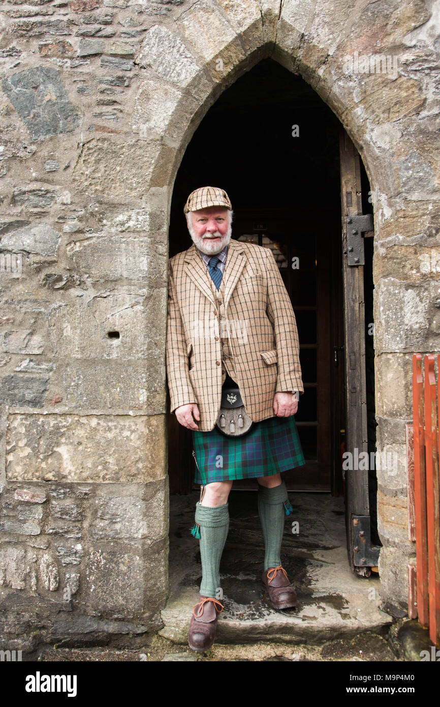 Portrait of mature man wearing traditional kilt leaning on archway of Eilean Donan Castle, Scotland, UK - Stock Image