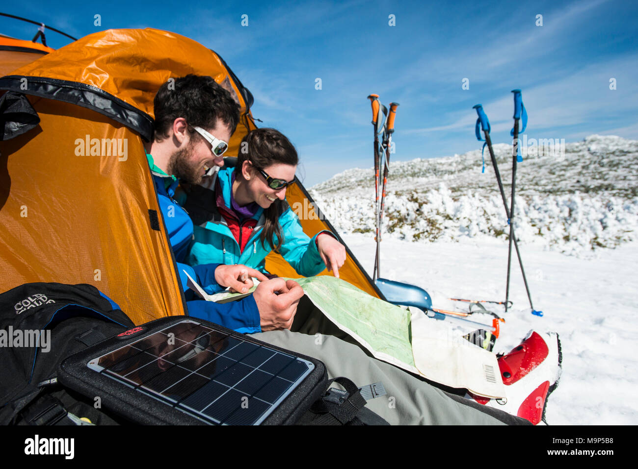Man and woman setting up campsite in winter in mountains during daytime, New Hampshire, USA - Stock Image