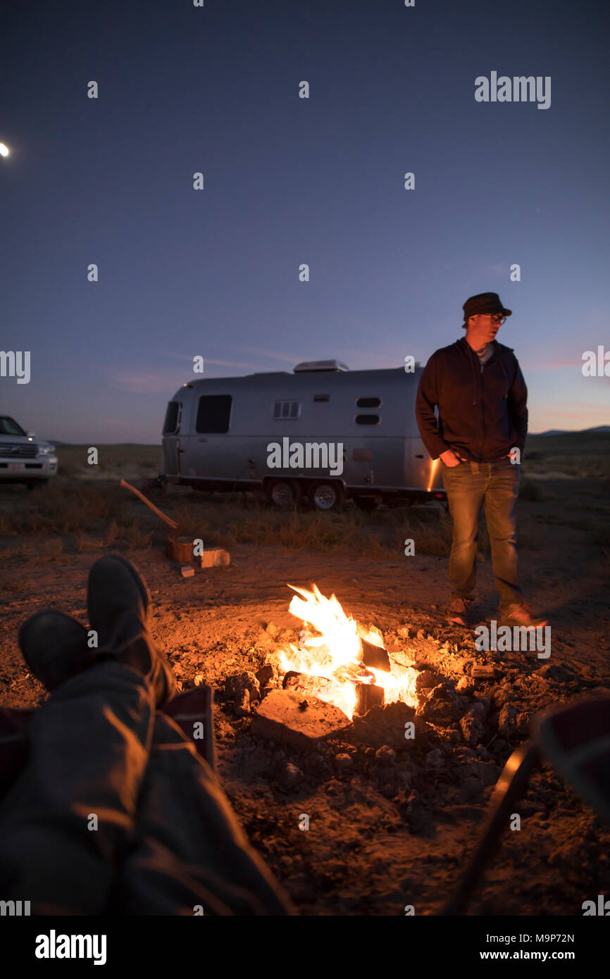 Personal perspective shot of campers around campfire at night, Winnemucca Lake, Nevada, USA - Stock Image