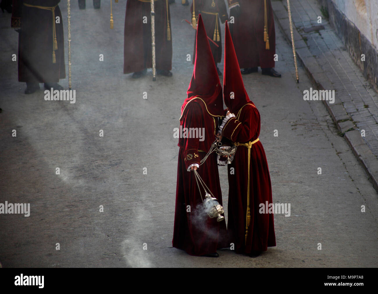Altar servers wearing red clothing and pointed hoods talking during Easter Week celebrations in Baeza, Jaen Province, Andalusia, Spain - Stock Image