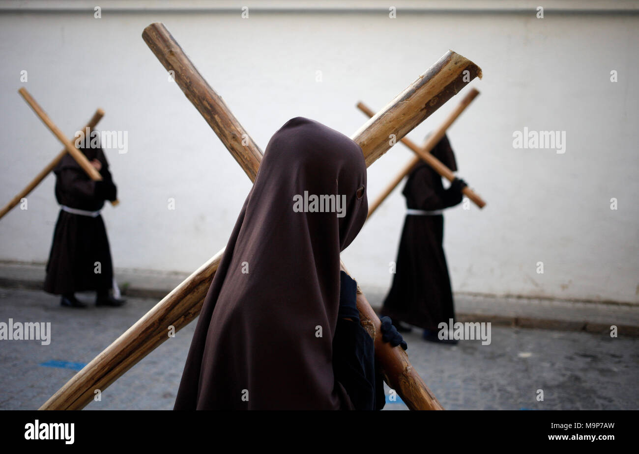 Hooded penitents carry crosses during Easter Week celebrations in Baeza, Jaen Province, Andalusia, Spain - Stock Image