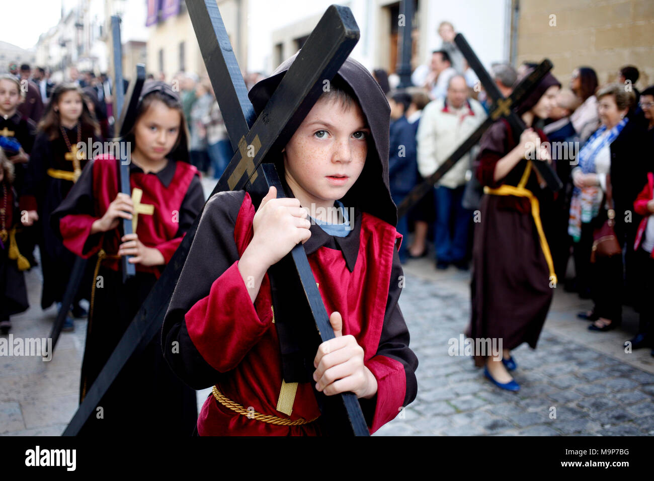 Boys and girls carrying crosses during Easter Week celebrations in Baeza, Jaen Province, Andalusia, Spain - Stock Image