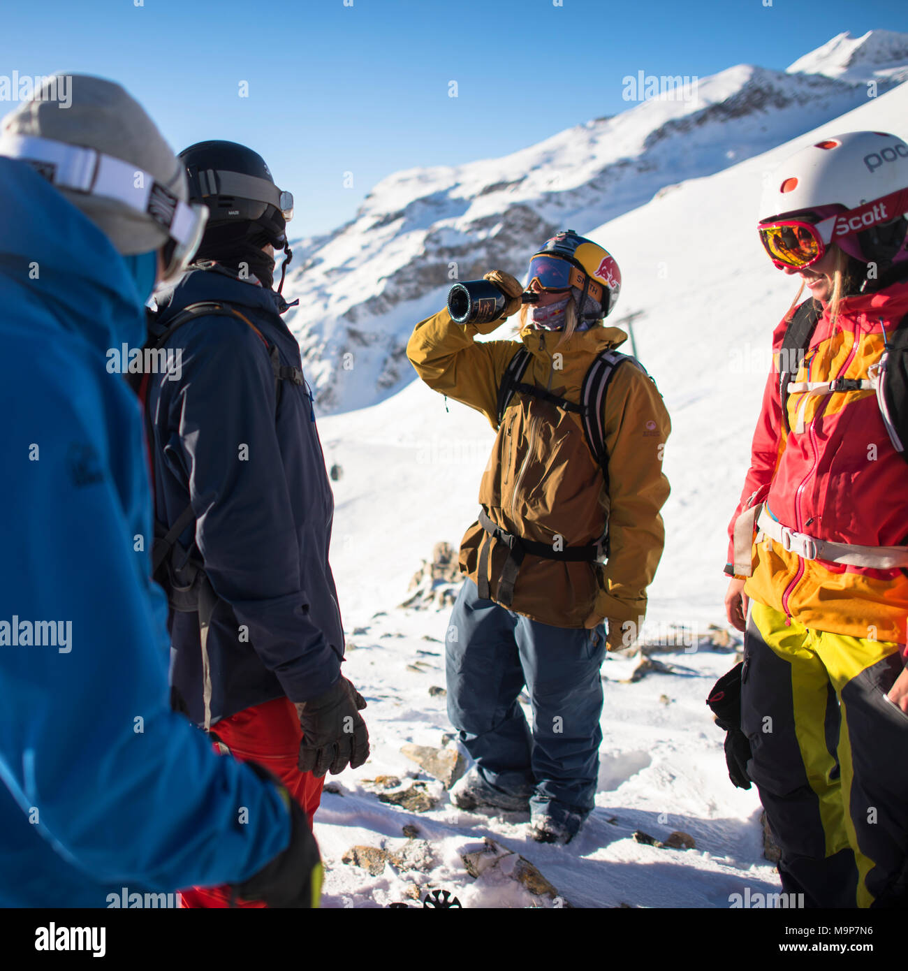 Professional skiers wearing skiwear, one drinking, Monterosa Ski mountain resort in Gressoney, Aosta, Italy - Stock Image