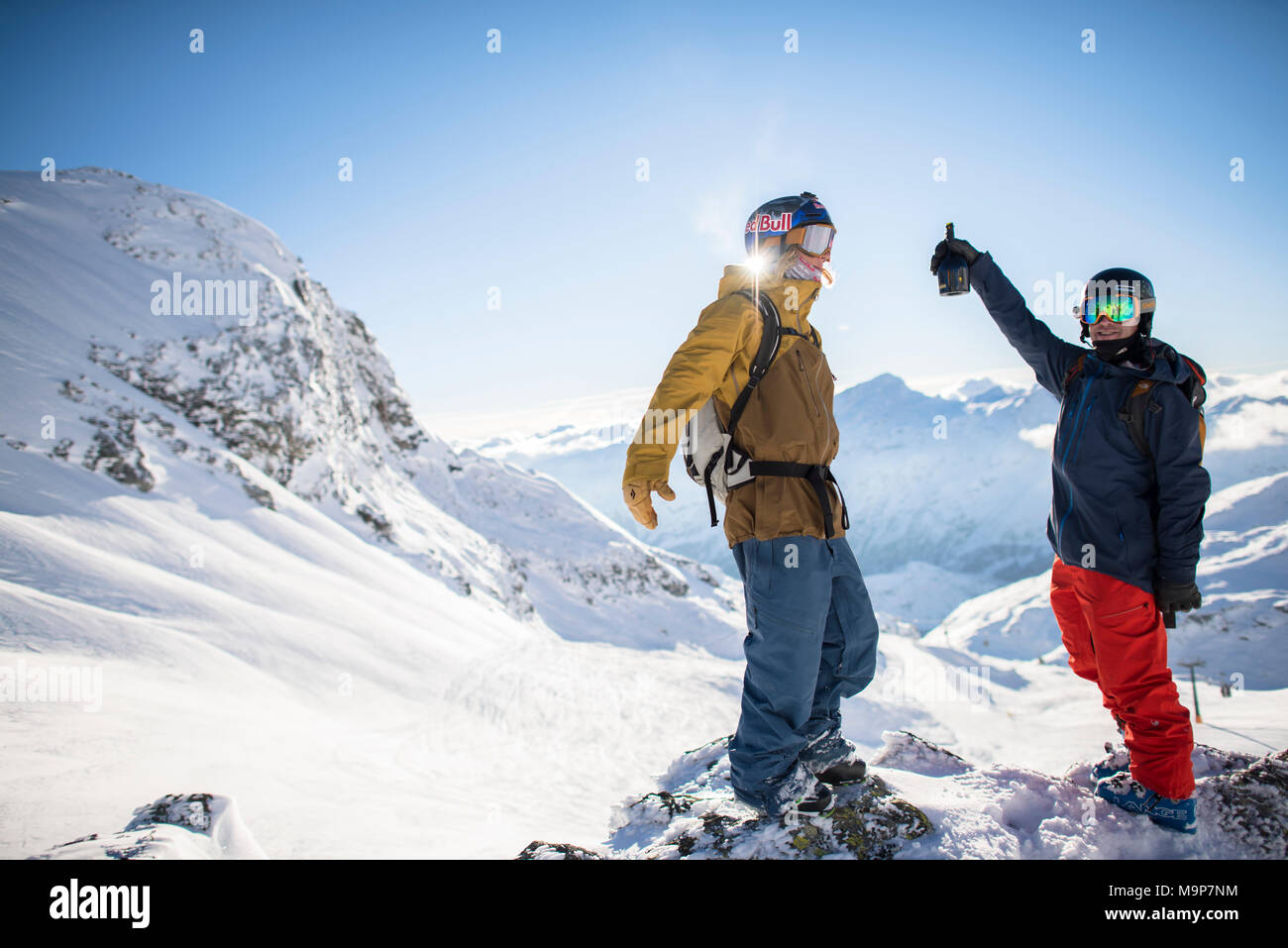 Professional skiers wearing skiwear and standing in winter scenery with mountains, Monterosa Ski mountain resort in Gressoney, Aosta, Italy - Stock Image