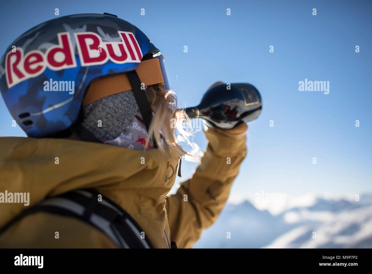 Skier in skiwear drinking wine from bottle, Monterosa Ski mountain resort in Gressoney, Aosta, Italy - Stock Image