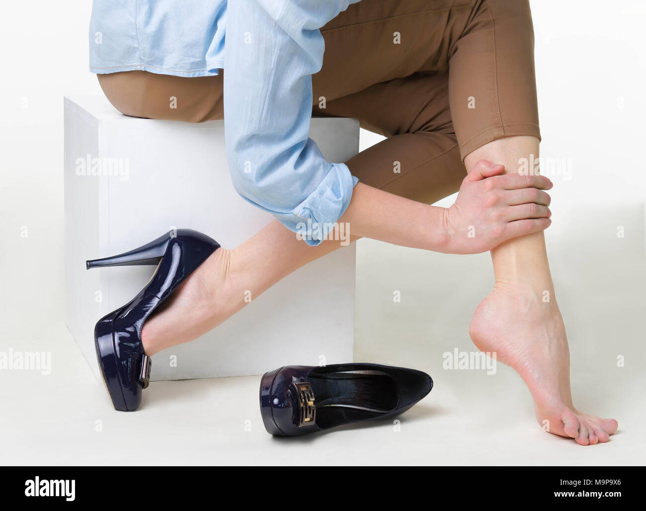 Cropped image of woman in high heels massaging her tired legs - Stock Image