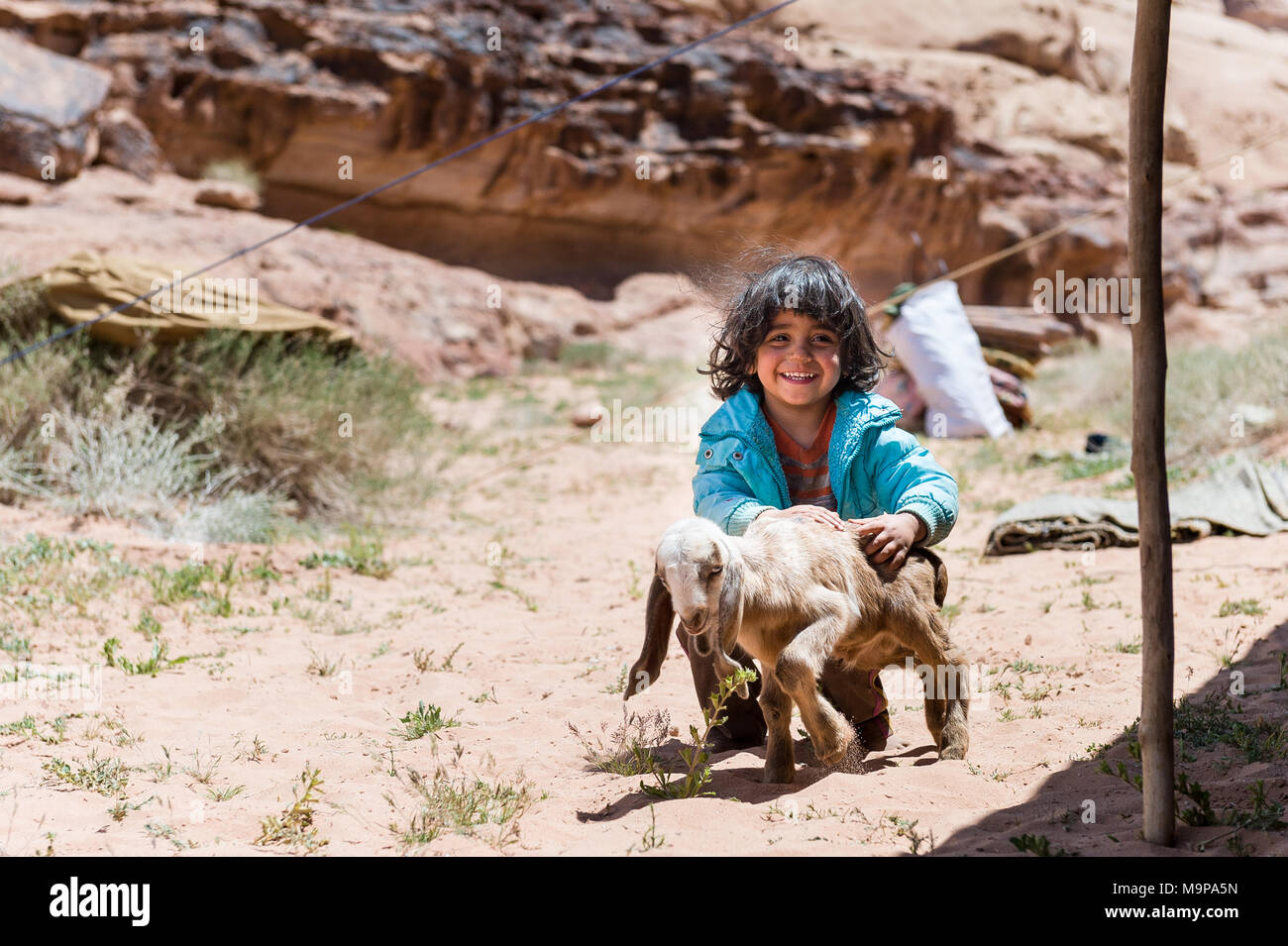 Young Bedouin girl playing with baby goat in the Wadi Rum desert near the border of Saudi Arabia. - Stock Image