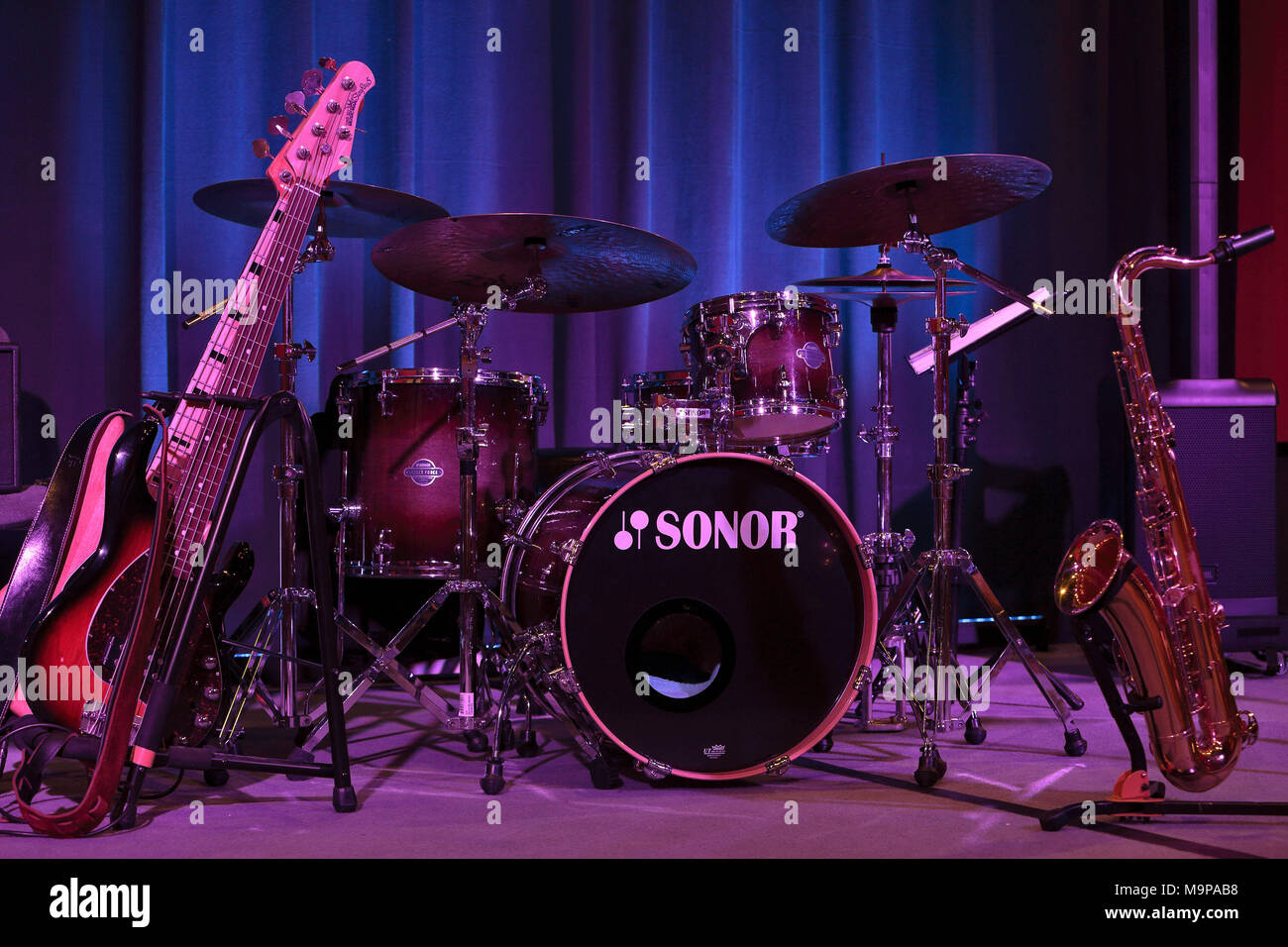 Instruments of a jazz band on stage, big band, electric bass, drums and saxophone - Stock Image