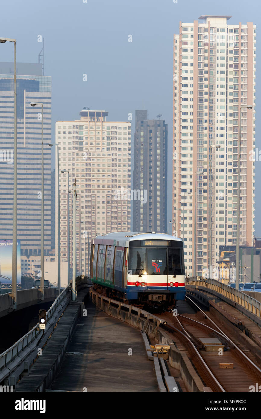 BTS Skytrain in front of skyscrapers, on Saphan Taksin Bridge, Sathon, Bangkok, Thailand - Stock Image