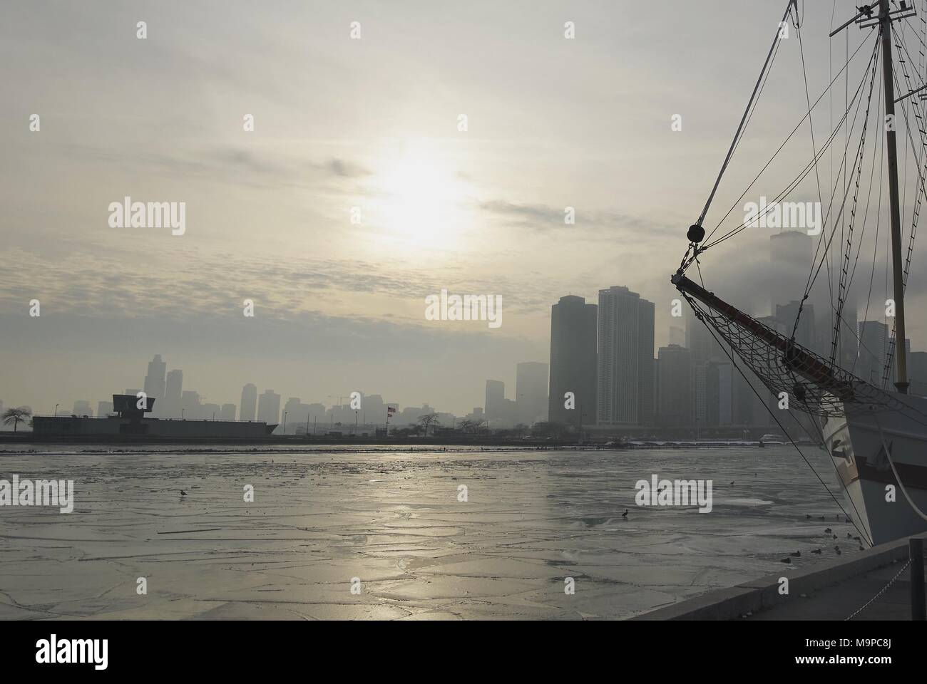 Chicago winter skyline over water with city and horizon over water and silhouette of ship mast in foreground - Stock Image