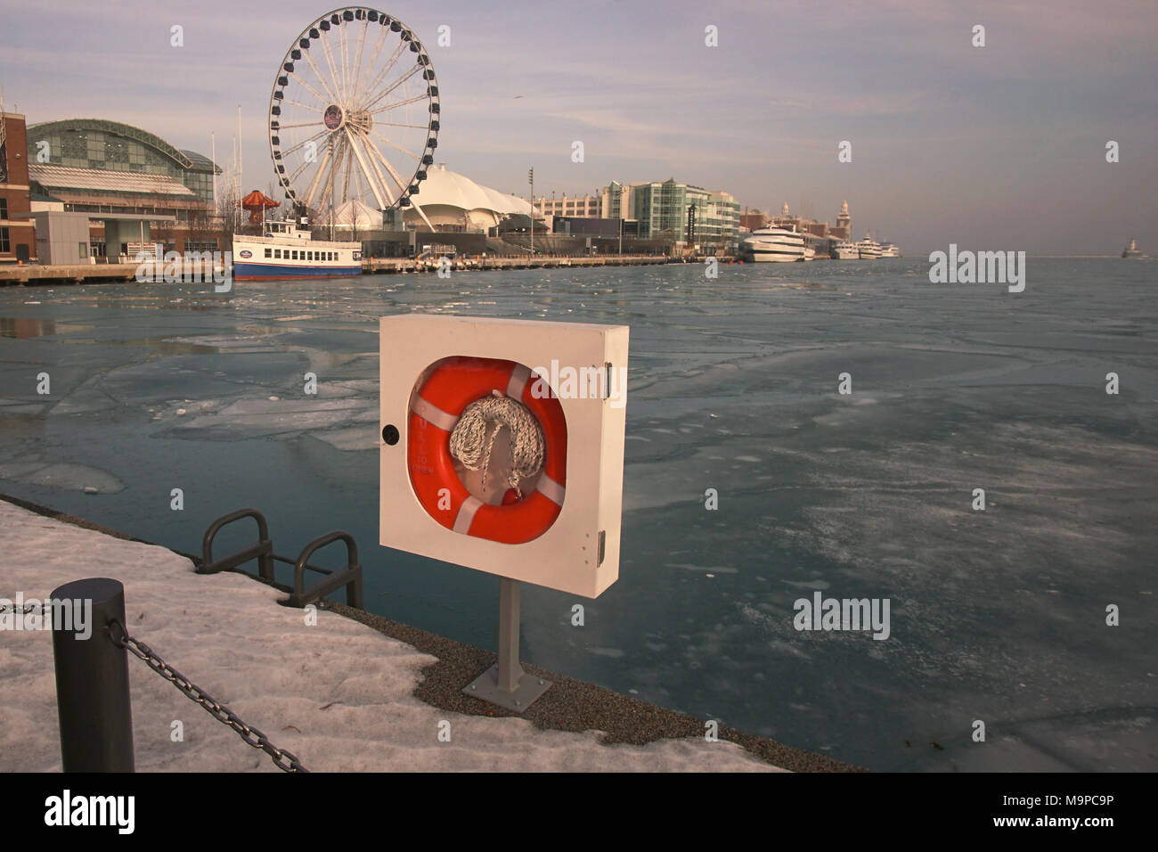 looking over the water on a winter day with view of Navy Pier and ferris wheel in distance, lifesaver device in foreground with snow on the ground - Stock Image