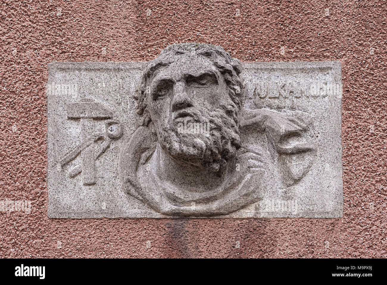 Relief of Vulcanus, roman god of fire and forge on a public building, Erlangen, Middle Franconia, Bavaria, Germany - Stock Image