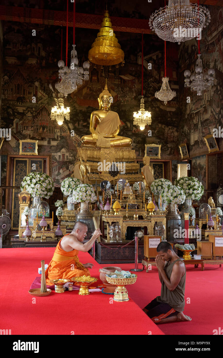 Buddhist monk blesses believers before handing over a lucky ribbon, Obosot of Wat Arun, Dawn Temple, Bangkok Yai, Bangkok - Stock Image