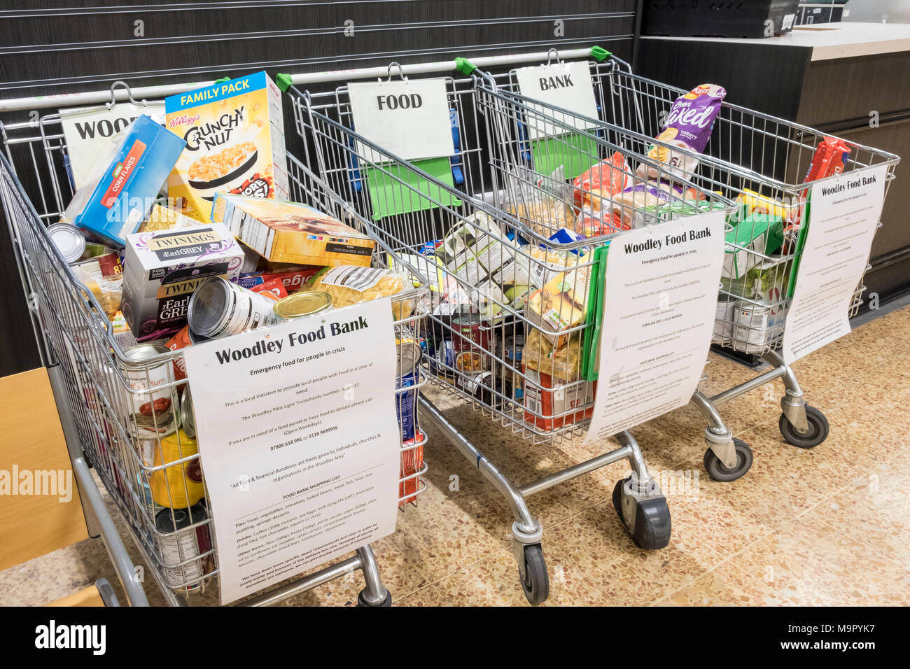 Food bank donations left in shopping trollies at an Asda supermarket. Reading, Berkshire, England, GB, UK - Stock Image