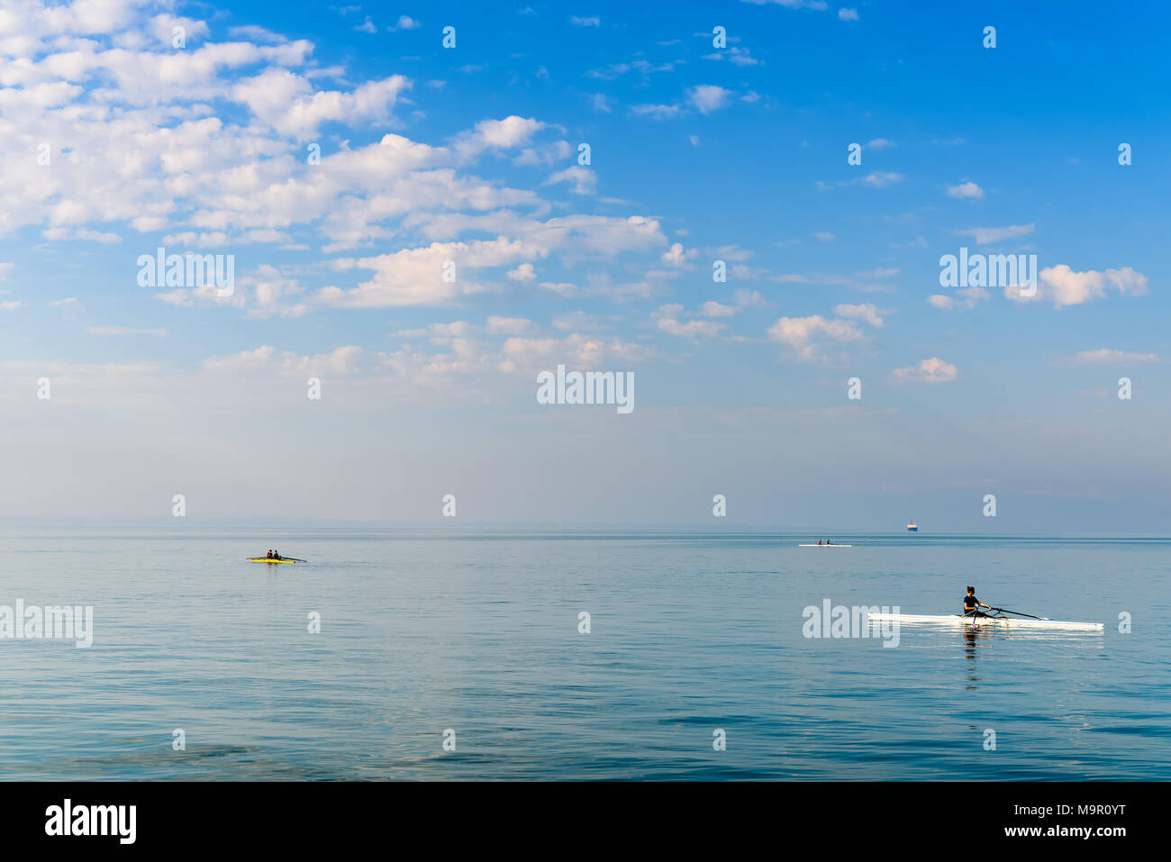 Thessaloniki, Greece - April 15, 2017: Rowers training early in the morning onto the calm waters of Aegean Sea, Thermaic Gulf - Stock Image