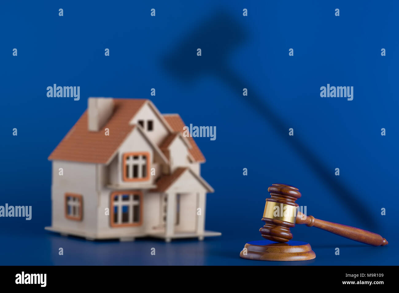 Gavel and model house on blue background. The gavel casts an ominous shadow over the house. Concept for house auction or real estate law Stock Photo