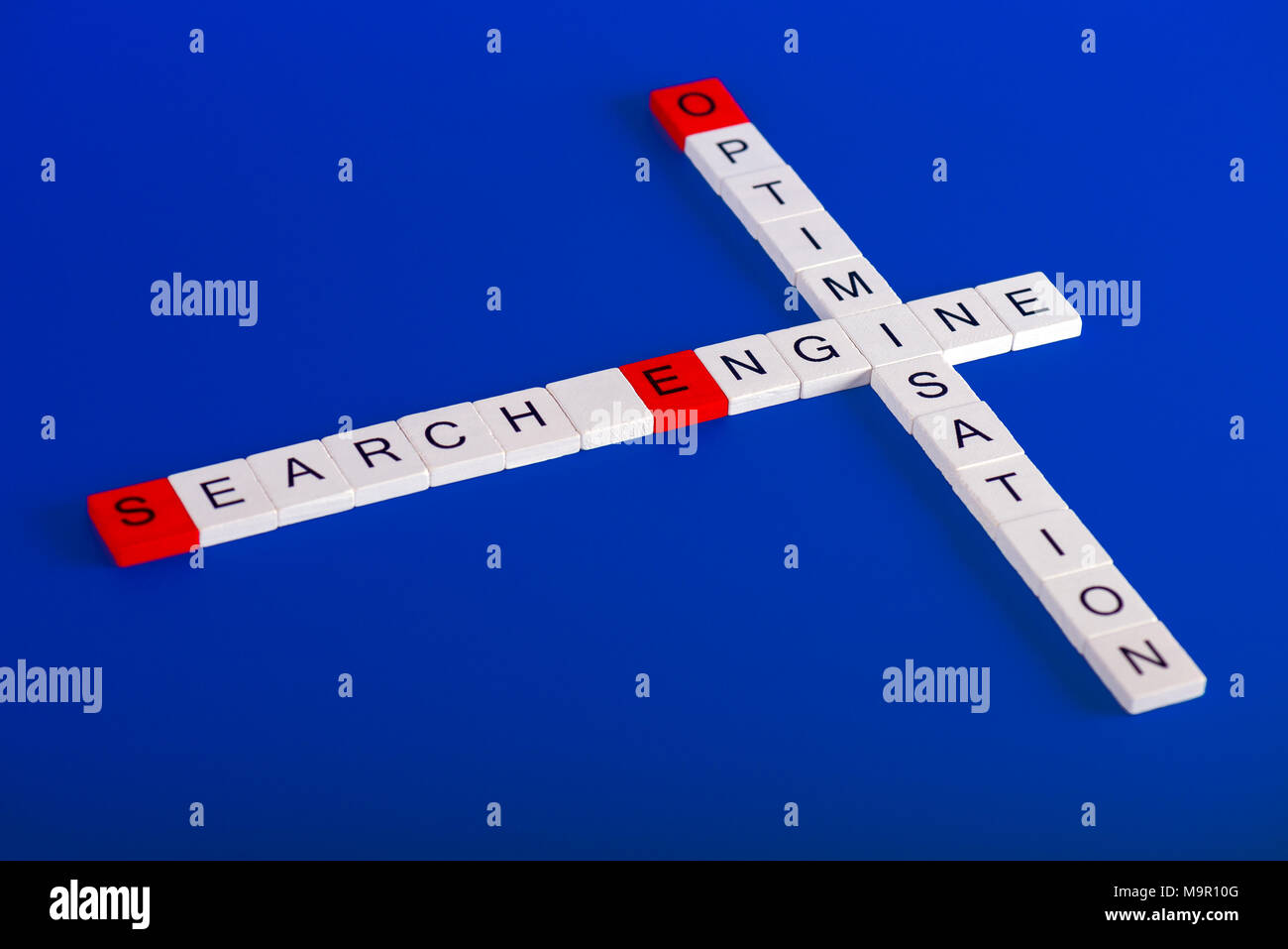 Search Engine Optimisation (SEO) made of white wooden blocks on blue background in crossword style, first letters are red - Stock Image