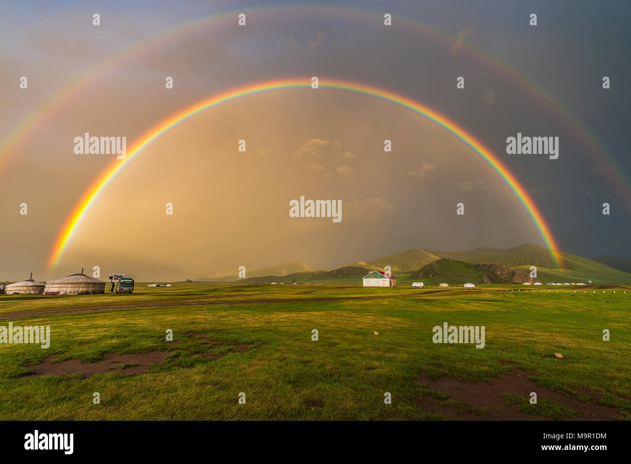 Double rainbow above nomad yurts in a green landscape, Mongolia - Stock Image