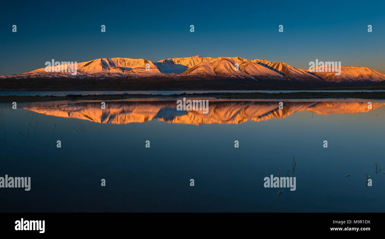 Khoton Lake, snow-covered mountains with dawn in the back, Mongolia - Stock Image