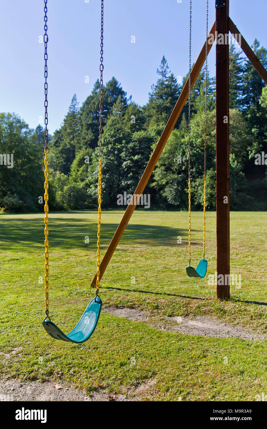 Two suspended vacant swings awaiting occupants, peaceful in the park. - Stock Image