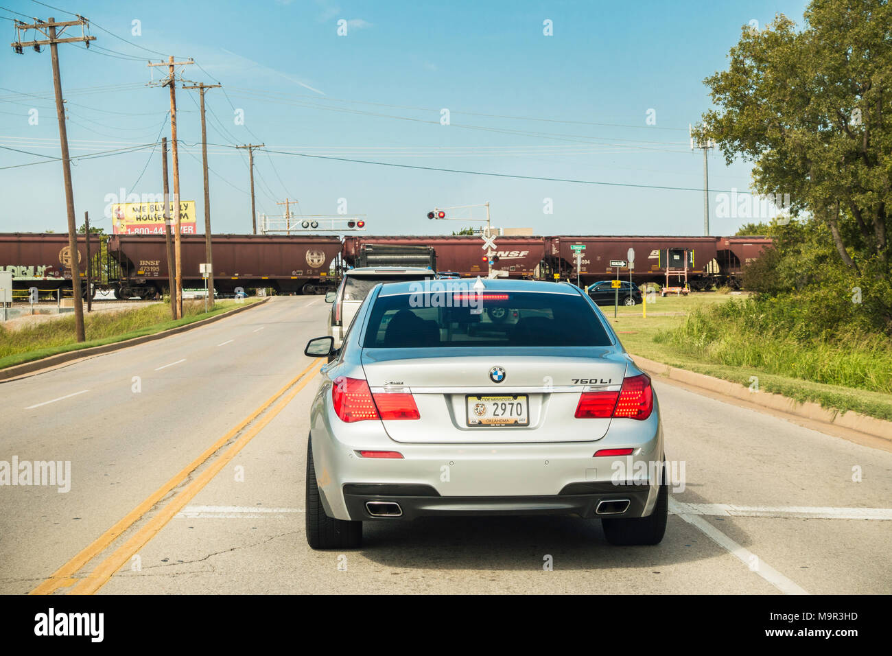 A line of automobiles waiting for a train to cross the road in Oklahoma City, Oklahoma, USA. - Stock Image