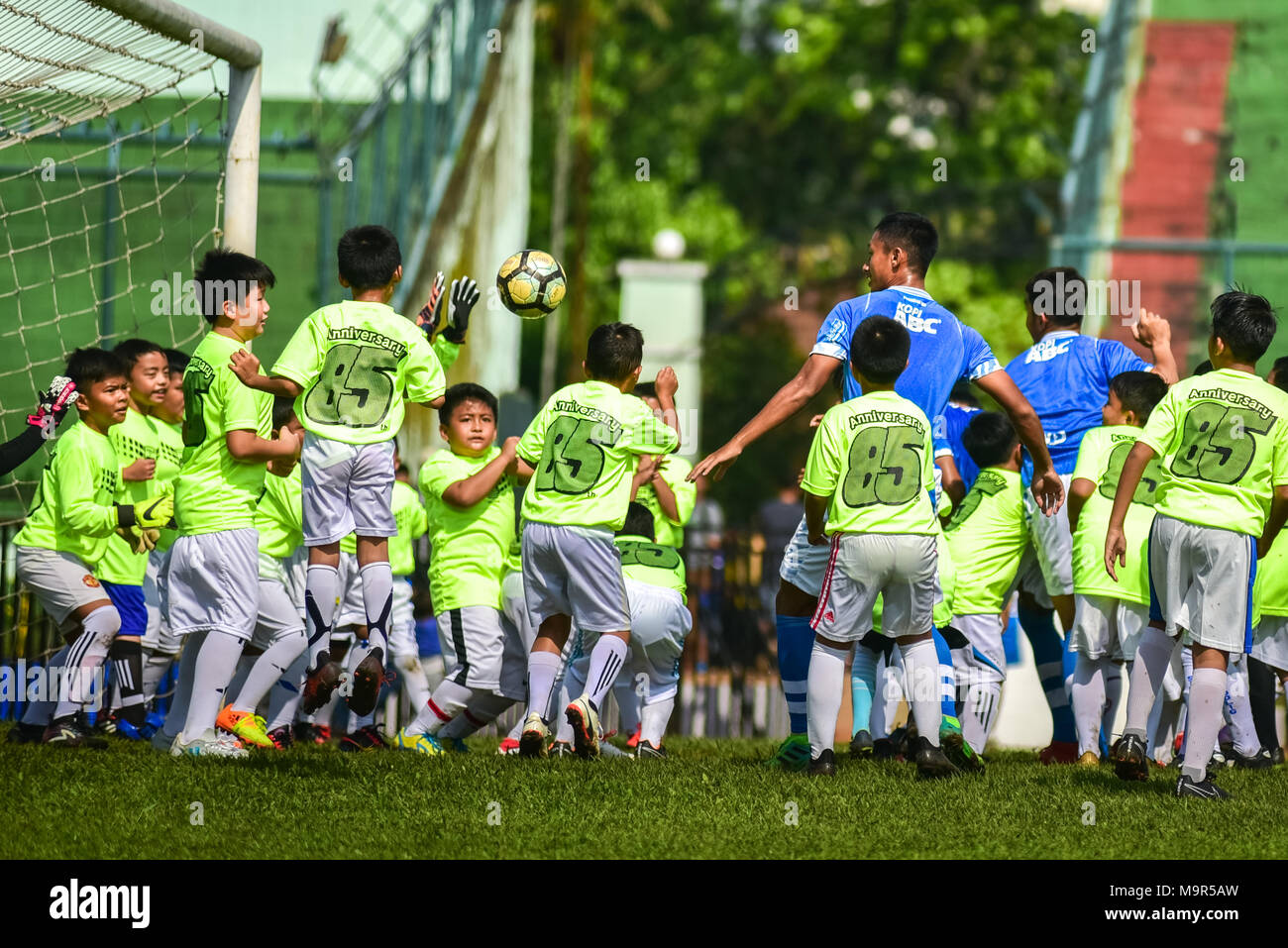 Five players of Indonesian football club of Persib Bandung play against 85 children in an exhibition match to celebrate its 85th anniversary. - Stock Image