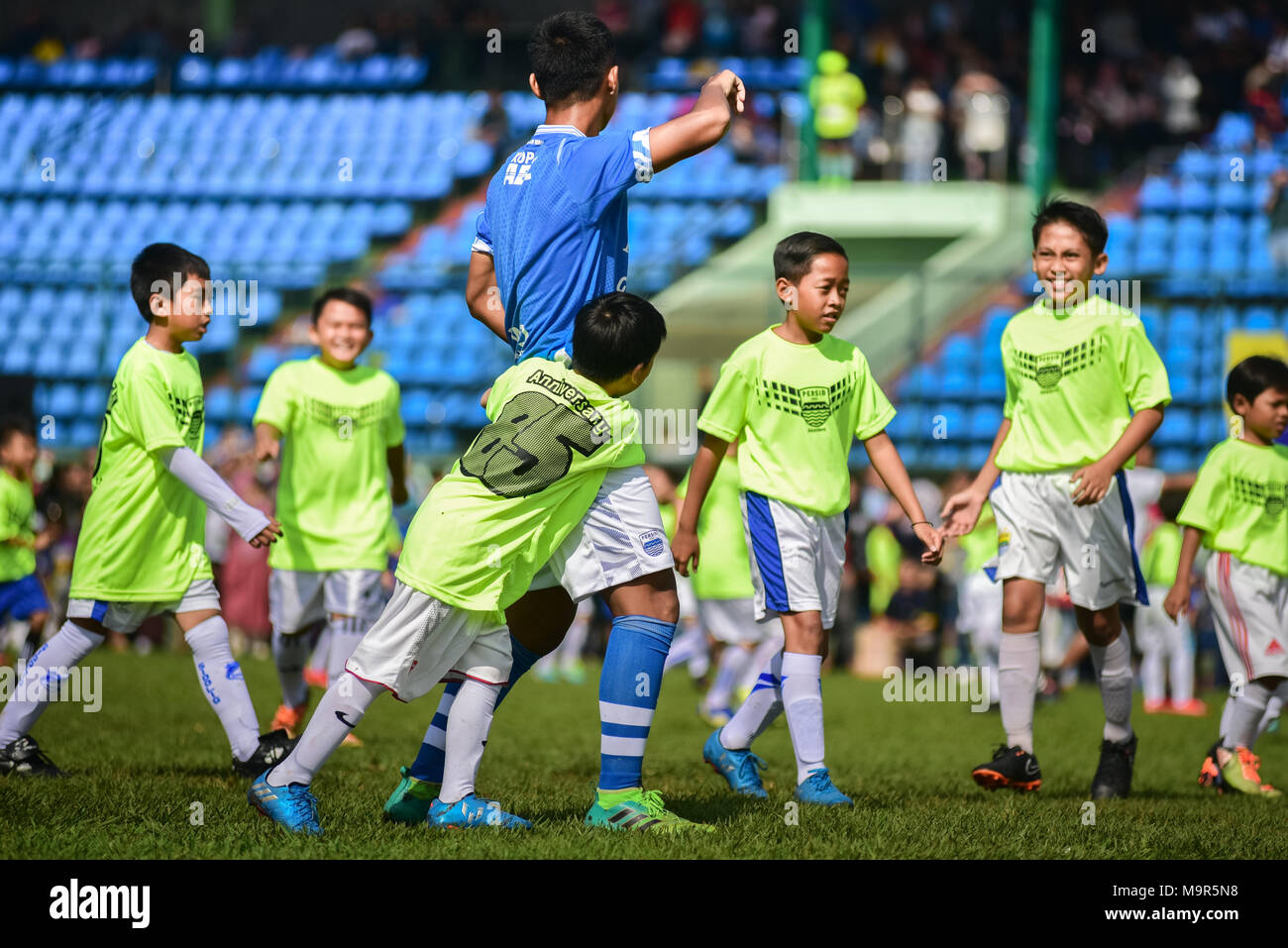 A child player doing a 'man to man marking' during an exhibition match to celebrate Persib FC's 85th anniversary in Bandung, Indonesia. - Stock Image