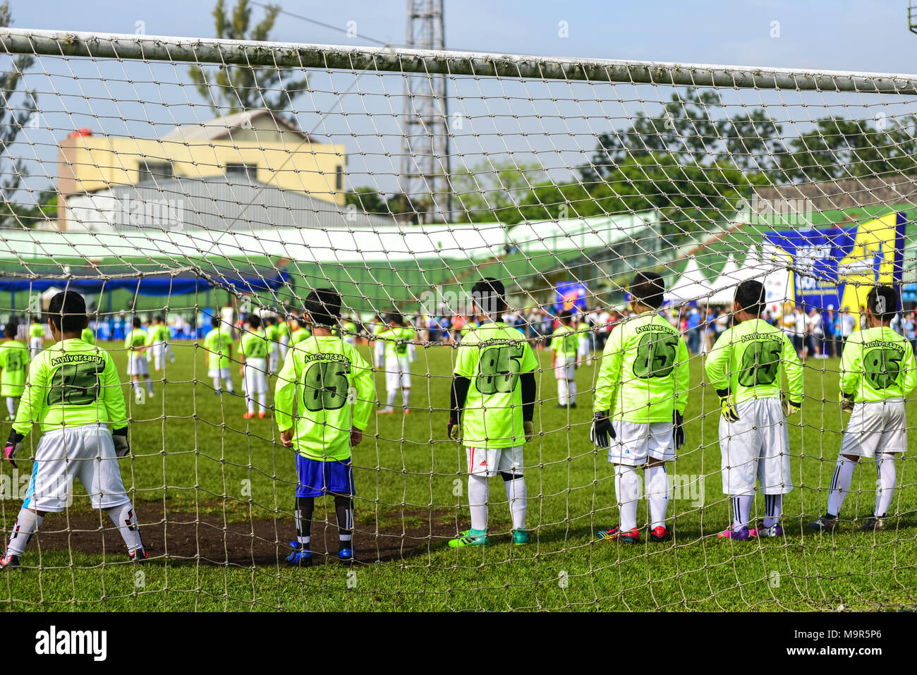 Six football academy trainees take the goalkeeper role in an exhibition match against Indonesian football club of Persib Bandung. Five players of Pers - Stock Image