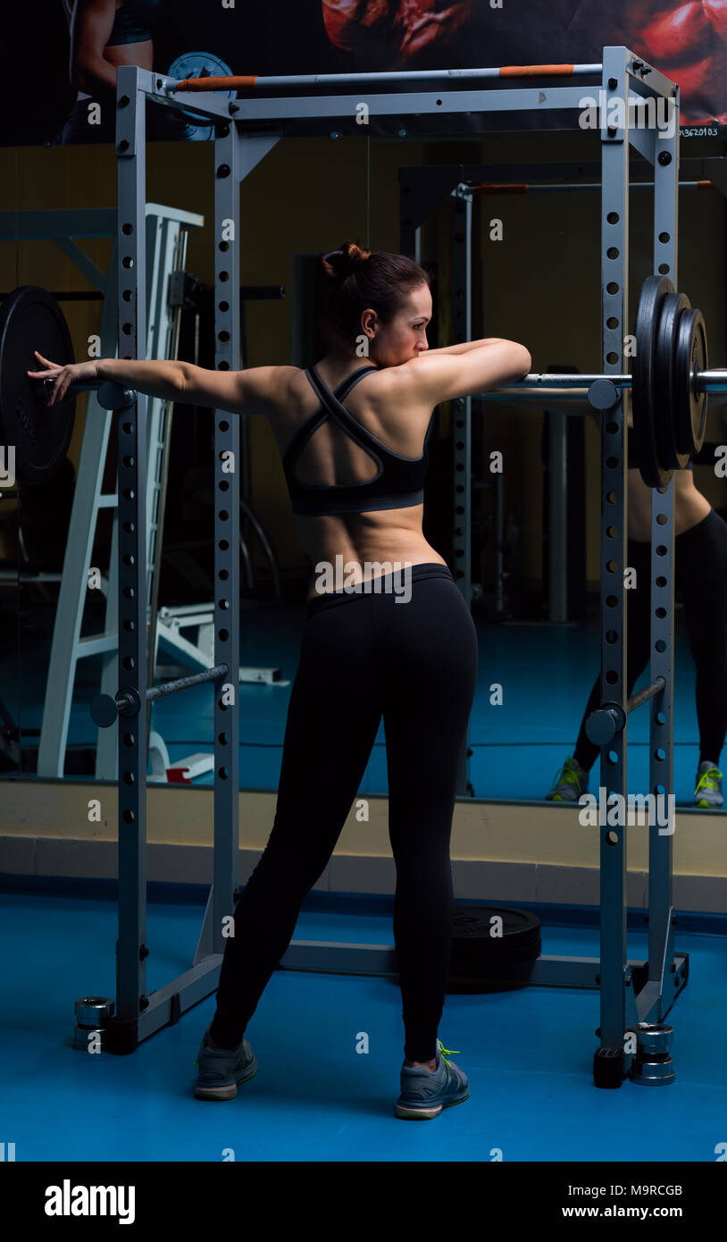 Woman with the barbell in the gym  - Stock Image