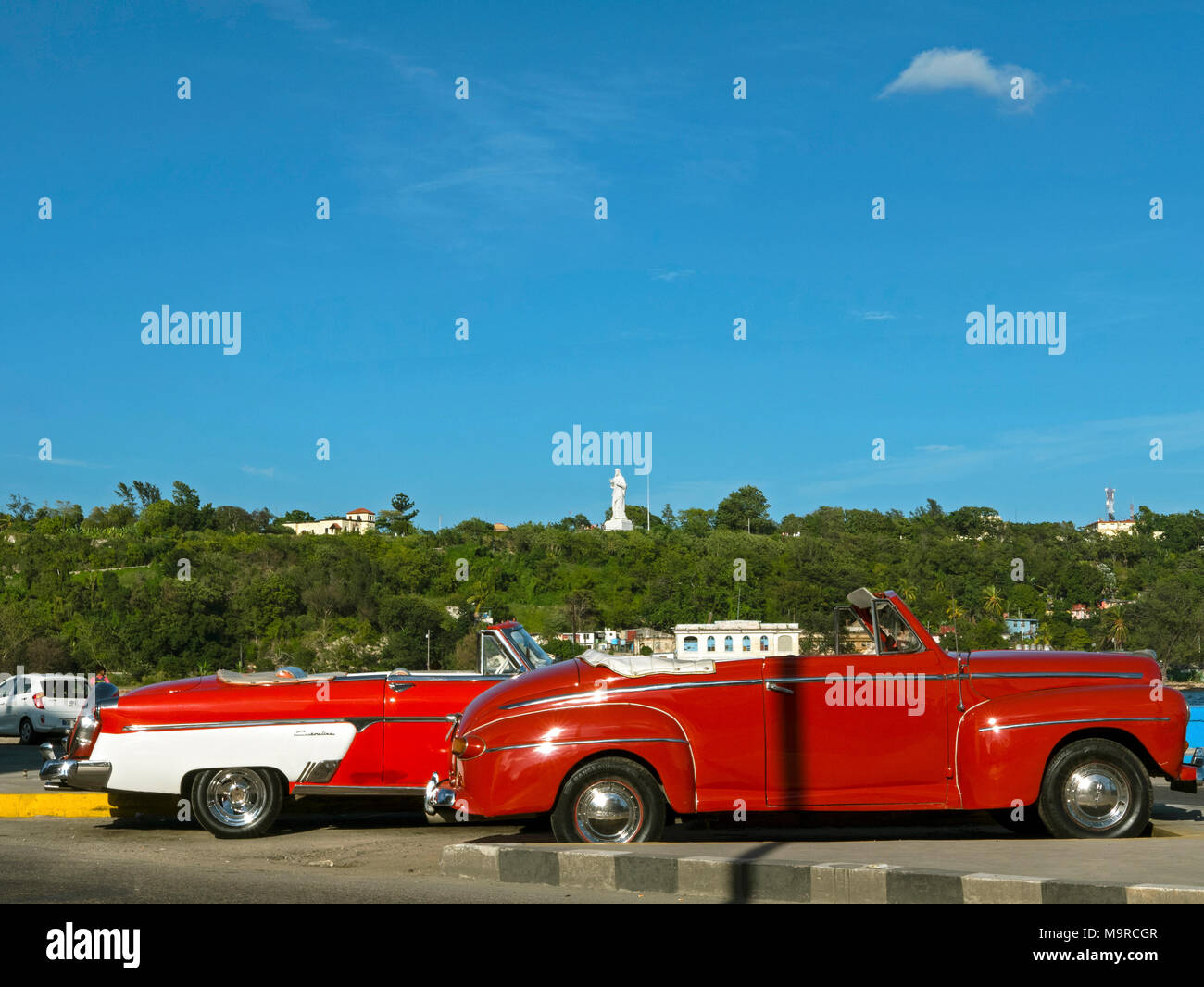 Red Vintage Convertibles on Havana Harbour with statue of Christ in background - Stock Image