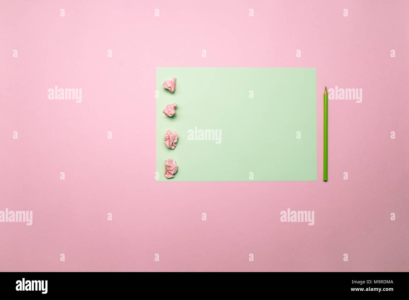 Two tone pink and green contrast color paper background with crumpled balls and pencil. Empty blank for text, design and advertising. - Stock Image
